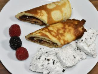 Süße Pfannkuchen mit Nuss-Nougat-Creme, Vanilleeis und Früchten.