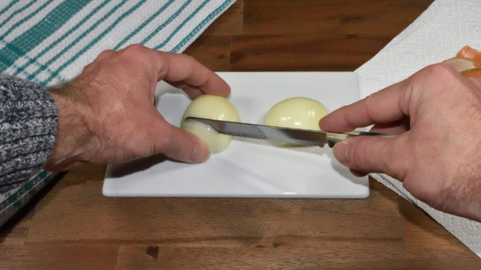 Die Zwiebel wird fächerförmig vertikal eingeschnitten.