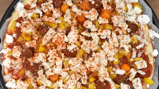 Fruchtige Tomaten-Feta-Pizza - backfertig belegt | Die fertig belegte Pizza freut sich schon auf den Ofen - und Veggie Tobi aufs Essen. :-)
