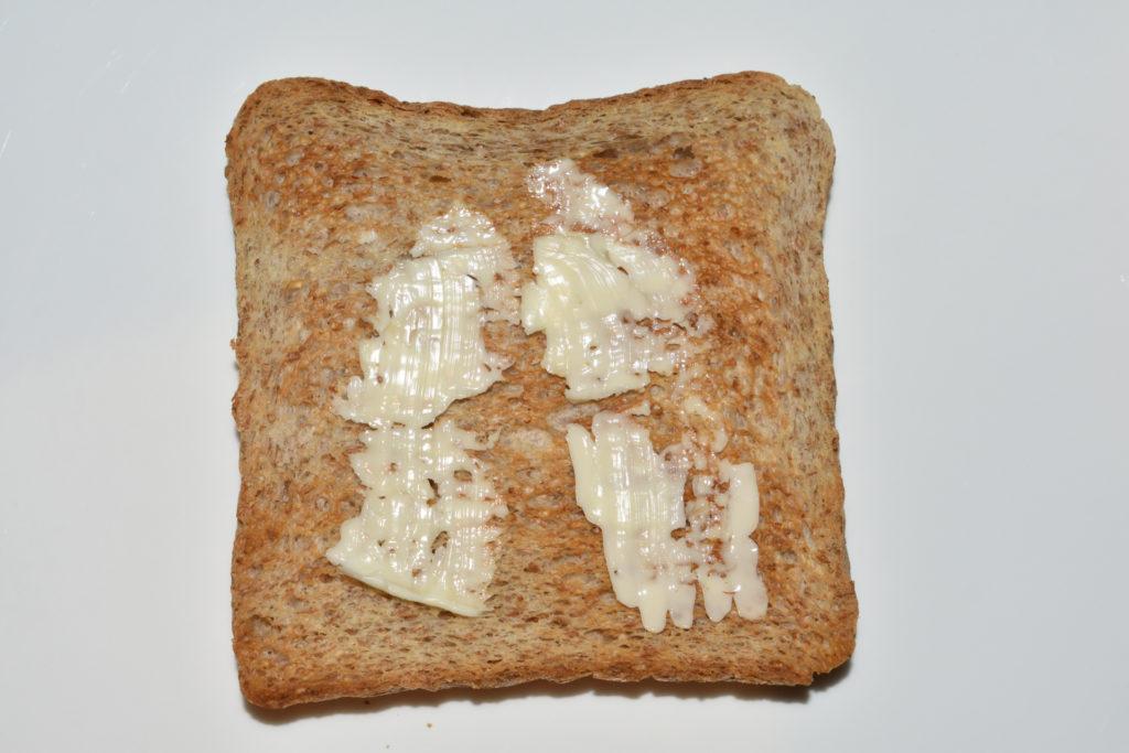 Croque Monsieur - Schicht für Schicht erklärt | Schritt 1: Bestreiche eine geröstete Toastscheibe einseitig mit Butter.