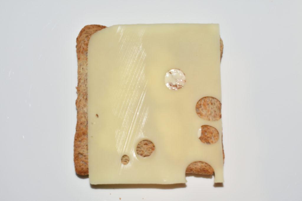 Croque Monsieur - Schicht für Schicht erklärt | Schritt 2: Lege nun eine Scheibe Käse darauf. Sie sollte an den Seiten nur wenig überstehen.