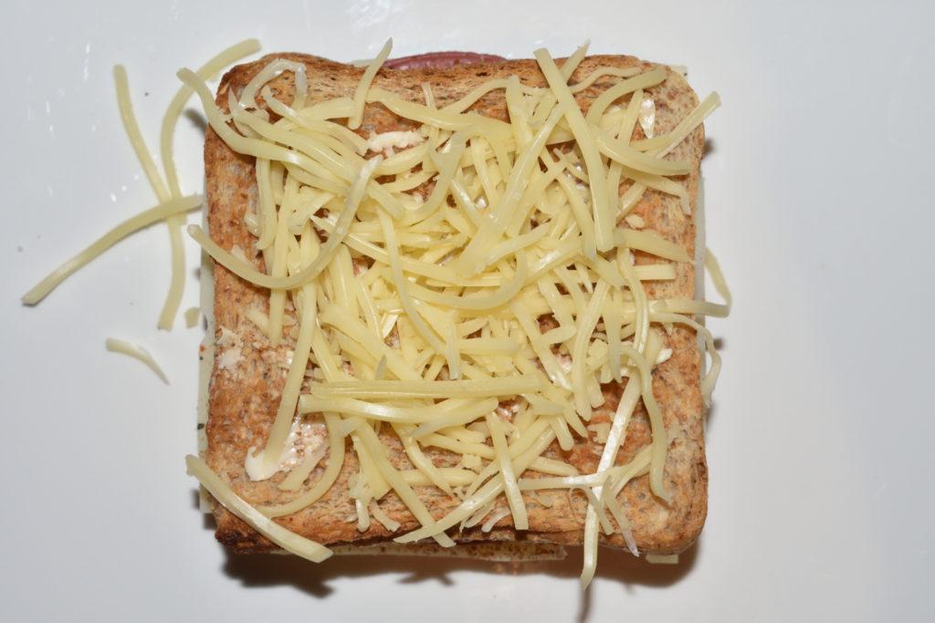 Croque Monsieur - Schicht für Schicht erklärt | Schritt 8: Bestreue den Toast mit geriebenem Emmentaler. Puh, geschafft ! Der Croque Monsieur ist beinahe fertig.