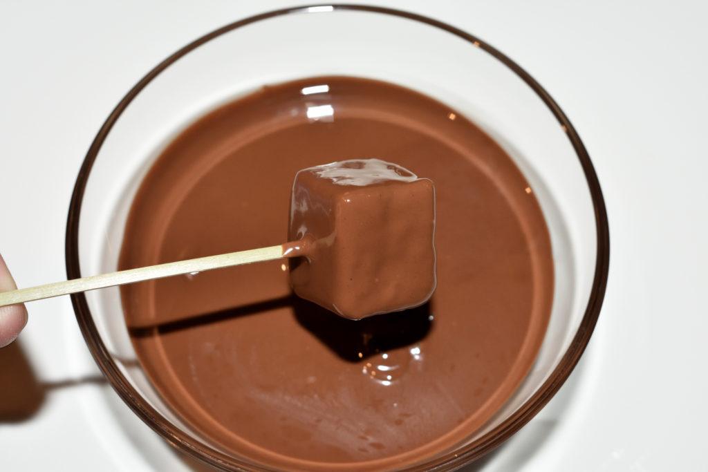 Lebkuchen-Pralinen: So wird's gemacht... 3/3   Die gewürfelten Soßenkuchen in geschmolzene Kuvertüre tauchen, kurz abtropfen lassen und zum Trocknen auf ein Stück Backpapier legen.