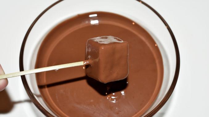 Lebkuchen-Pralinen: So wird's gemacht... 3/3 | Die gewürfelten Soßenkuchen in geschmolzene Kuvertüre tauchen, kurz abtropfen lassen und zum Trocknen auf ein Stück Backpapier legen.