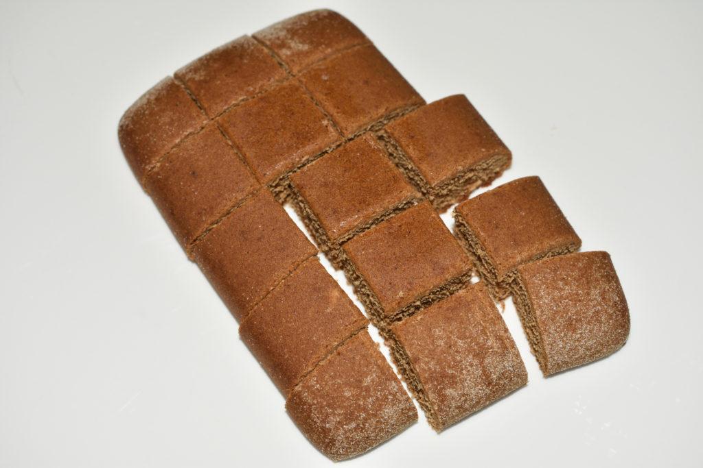 Lebkuchen-Pralinen: So wird's gemacht... 2/3   Den Soßenkuchen in kleine Stückchen schneiden (ca. 15 pro Scheibe). Bei Bedarf die abgerundeten Kanten entfernen. Mit etwas Alkohol beträufeln.