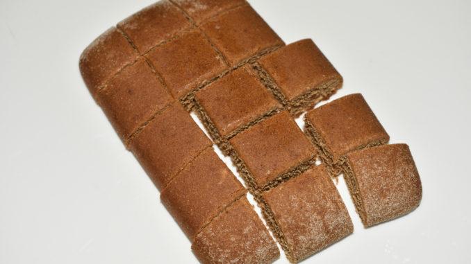 Lebkuchen-Pralinen: So wird's gemacht... 2/3 | Den Soßenkuchen in kleine Stückchen schneiden (ca. 15 pro Scheibe). Bei Bedarf die abgerundeten Kanten entfernen. Mit etwas Alkohol beträufeln.