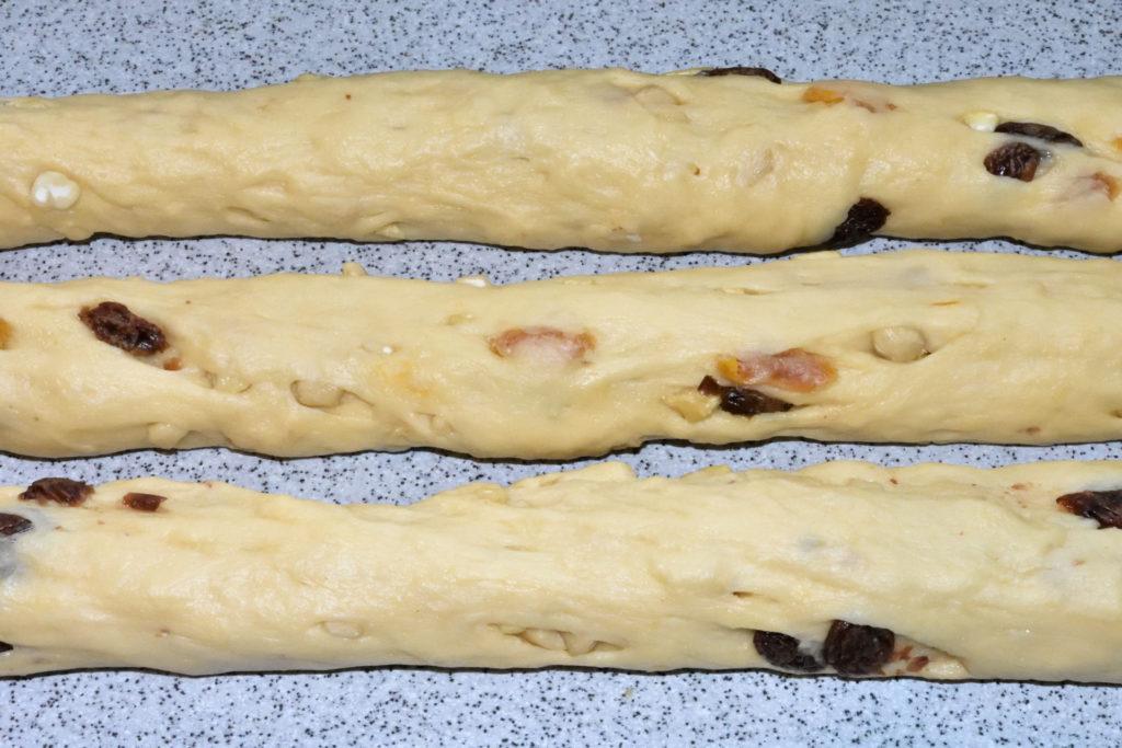 Cashew-Hefezopf - so wird's gemacht... (4/4) | Jetzt rollst Du die Kugeln zu Strängen, drückst ihre Enden zusammen und flechtest aus den dreien einen Zopf (immer abwechselnd einen äußeren Strang über den mittleren schlagen).