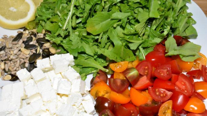 Lauter leckere Zutaten für meinen Salat: Rucola, Partytomaten, Fetakäse, Salat-Kernmischung und Zitrone.
