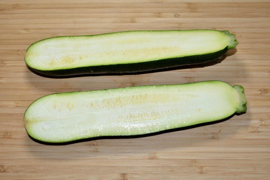 Zucchini richtig füllen - so geht's (2/6) | Die Zucchino wird mit einem scharfen Messer der Länge nach halbiert. Arbeite dabei möglichst akkurat, sonst kippen die Schiffchen später beim Füllen um.