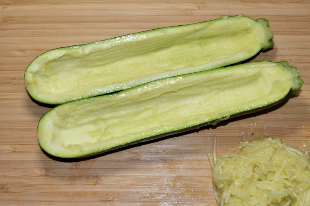 Zucchini richtig füllen - so geht's (3/6) | Jetzt kommt der schwierige Teil: Mit einem Teelöffel, besser aber mit einem Kugelausstecher oder einem Zestenreißer, entfernst Du vorsichtig das Innere.