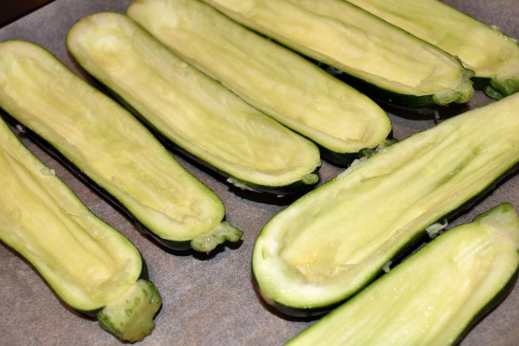 Zucchini richtig füllen - so geht's (5/6) | Zucchini im Akkord entkernen kann schon ein paar Minütchen dauern... danach wandern sie gleich zum Befüllen auf das mit Papier ausgelegte Backblech.