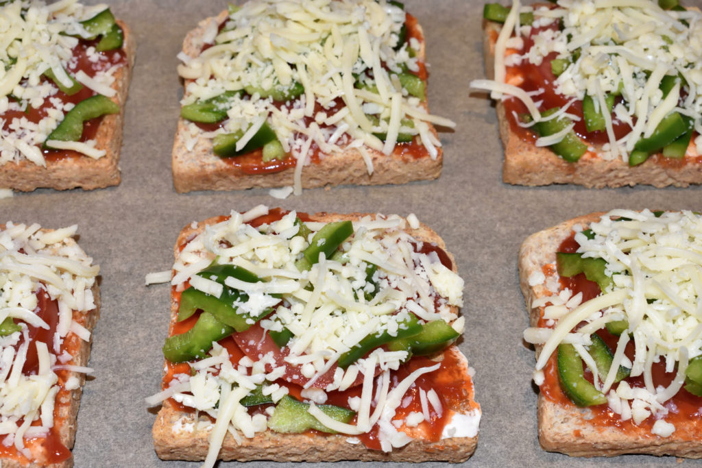 Schon fast fertig...   Die fertigen Toastpizzen kommen auf ein Backblech. Neun Stück sollten in einen Ofen mit Standardmaßen passen.