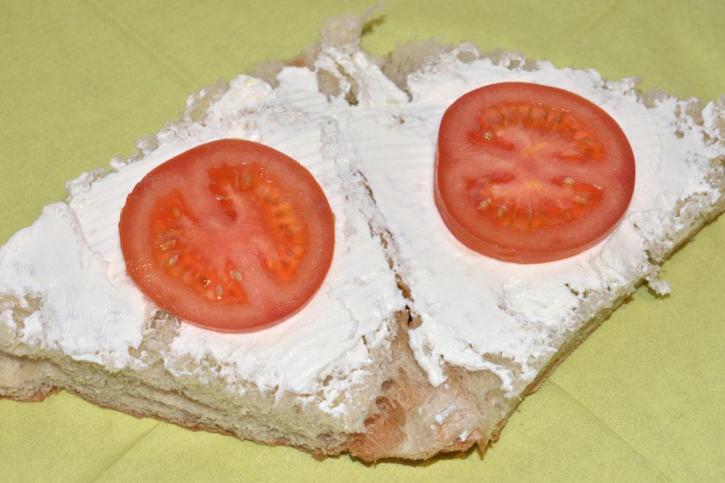 Gefülltes Fladenbrot - so wird's gemacht   Nach dem Quark kommen zwei strategisch platzierte Scheiben Tomaten aufs Brot.