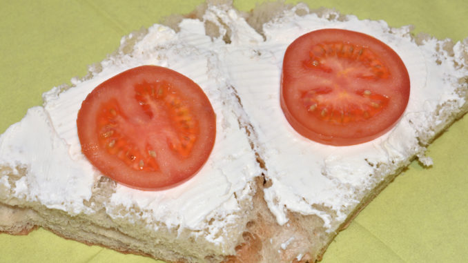 Gefülltes Fladenbrot - so wird's gemacht | Nach dem Quark kommen zwei strategisch platzierte Scheiben Tomaten aufs Brot.