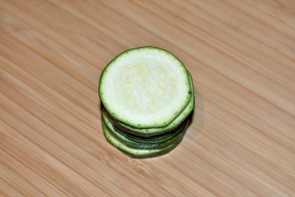 Zucchinis einfach würfeln - Schritt 1/3 | Als erstes schneidest Du die Zucchini in drei bis fünf Millimeter dicke Scheiben. Die Endstücke werden nicht gebraucht (darfst Du ganz allein aufessen).