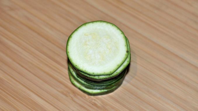 Zucchinis einfach würfeln - Schritt 1/3   Als erstes schneidest Du die Zucchini in drei bis fünf Millimeter dicke Scheiben. Die Endstücke werden nicht gebraucht (darfst Du ganz allein aufessen).