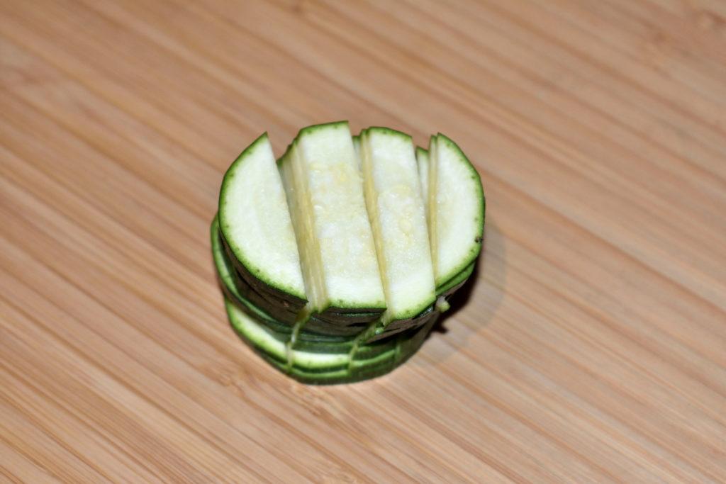 Zucchinis einfach würfeln - Schritt 2/3 | Jetzt kommt mein Geheimtrick: Nimm Dir jeweils eine Handvoll Zucchinischeiben, bau ein Türmchen und schneide es in Streifen.