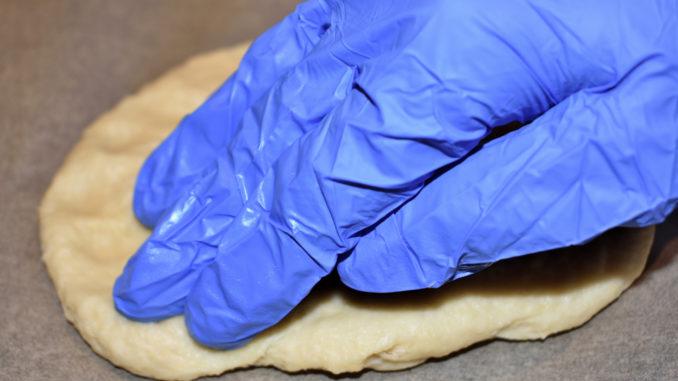 Pizzaboden vorbereiten - 2/3 | Jetzt drückst Du mit dem Handballen und den Fingern den Kloß von innen nach außen zum Blechrand hin glatt.