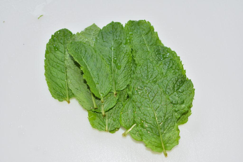 Pfefferminze hacken - Schritt 1/3 | Am besten zupfst Du die Blätter frisch von der Pflanze und spülst sie kurz unter fließend kaltem Wasser ab. So bleibt der volle Geschmack erhalten.