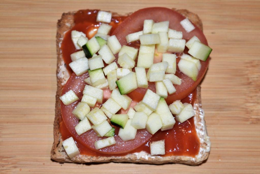 Pizzatoast mit Zucchini - so wird's gemacht... | Schritt 4: Jetzt belegst Du den Toast mit Tomatenscheiben und gewürfelten Zucchini. Nimm so viel davon, wie Du magst (und drauf passt).