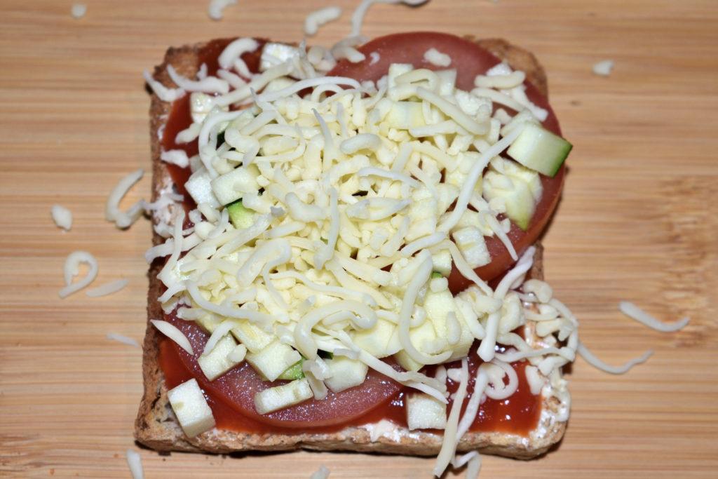 Pizzatoast mit Zucchini - so wird's gemacht... | Schritt 5: Zum krönenden Abschluss streue geriebenen Pizzakäse oder Gouda darüber. Das hält nicht nur den Belag zusammen, sondern schmeckt auch noch lecker.